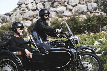 Portrait of two bikers standing with their sidecar motorcycle on a meadow - JASF000397