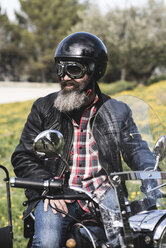 Portrait of biker wearing helmet and goggles sitting on his sidecar motorcycle - JASF000400