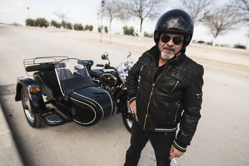 Portrait of cool biker wearing helmet and sunglasses standing on a road in front of his sidecar motorcycle - JASF000403