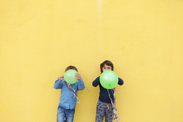 Two little boys with green balloons and streamers standing in front of yellow wall - VABF000143
