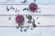 Two glasses of chia blueberry pudding and two tea spoons on wood - LVF004518