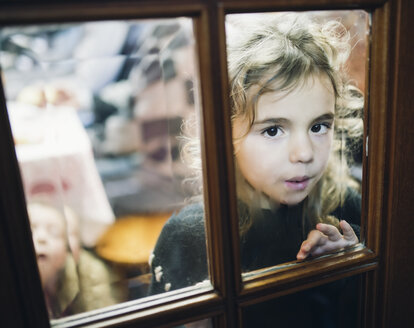 Portrait of little girl looking through a glass pane of a door - RAEF000870