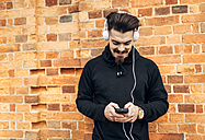 Portrait of young man in front of brick wall listening music with headphones - MGOF001431