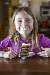 Portrait of happy girl with whipped cream on her lips and a stack of mini pancakes with chocolate - SARF002553