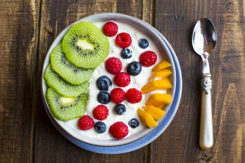 Bowl with yogurt and blueberries, kiwi, mango and raspberries, spoon on wood - SARF002560