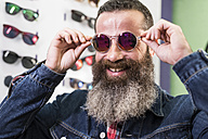 Smiling bearded man in optical store trying on sunglasses - JASF000413