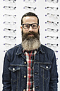 Bearded man in optical store trying on glasses - JASF000416