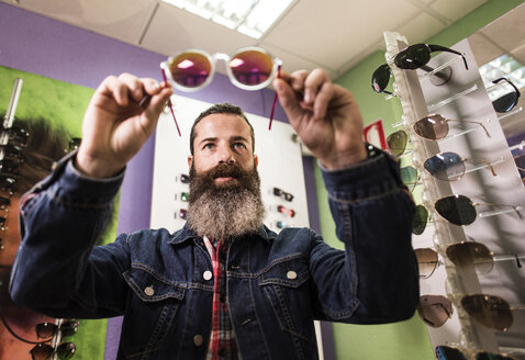Bearded man in optical store chosing sunglasses - JASF000419