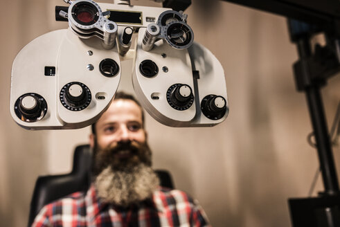 Bearded man making an eye test - JASF000422