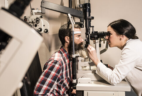 Optometrist examining eyes of a bearded man - JASF000425