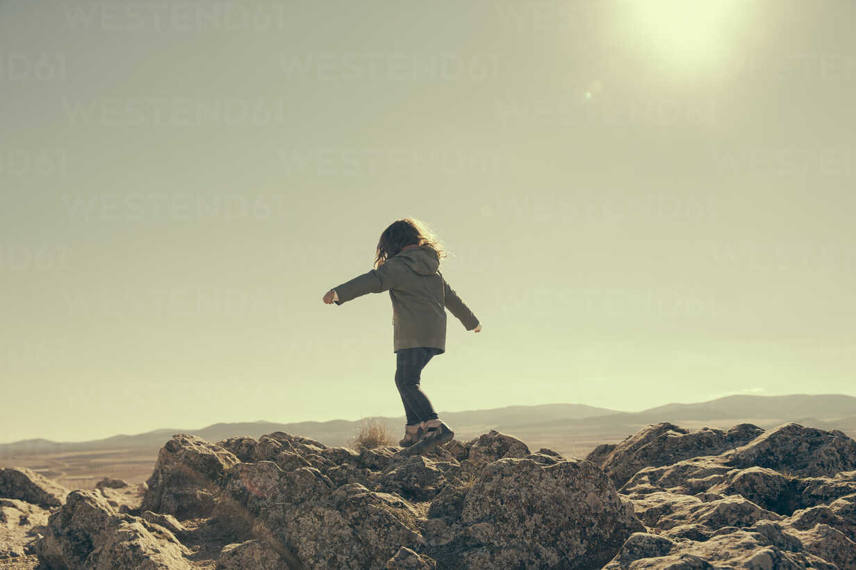 Spain, Consuegra, back view of little girl balancing on rocks in the mountains - ERLF000135 - Enrique Ramos/Westend61