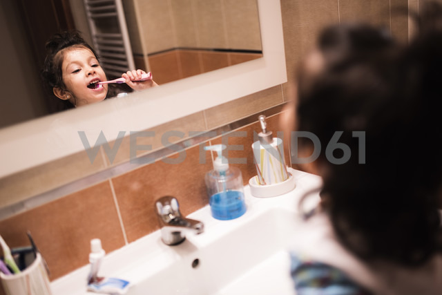 Mirror image of little girl standing in the bathroom brushing her teeth - JASF000434