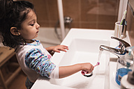 Little girl standing in the bathroom going to brush her teeth - JASF000437