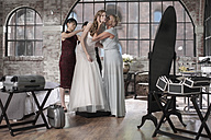 Mother and bridesmaid helping bride putting on wedding dress - ZEF008397