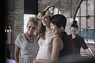 Bride getting ready for wedding with help of her mother and bridesmaid - ZEF008400