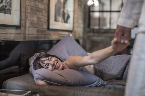 Smiling woman in bed looking at husband - ZEF008424