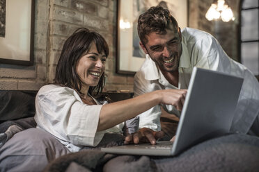 Happy couple together in bed looking at laptop - ZEF008433