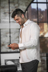 Smiling man in an apartment looking at phone while getting dressed - ZEF008436