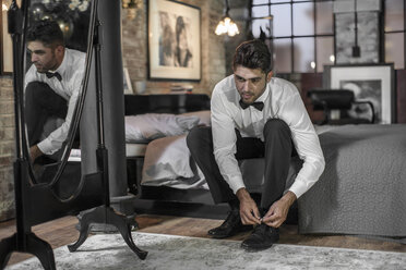 Man sitting on bed tying shoes - ZEF008448