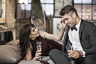 Smiling couple in elegant clothing drinking champagne in bed - ZEF008460