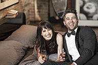 Happy couple in elegant clothing drinking champagne in bed - ZEF008463