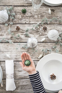 Girl's hand holding tea light in front of laid table at Christmas time - LVF004531