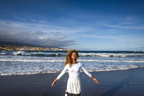 Spain, Tenerife, woman with closed eyes standing on the beach - SIPF000179