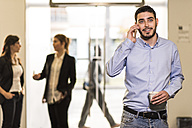 Young man in office talking on cell phone, holding cup of coffee - JASF000463