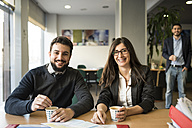 Portrait of smiling man and woman sitting at office desk with coffee - JASF000472