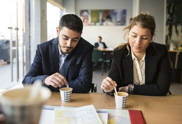 Man and woman sitting at office desk with coffee - JASF000475