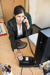 Woman on the phone at desk in office - JASF000481