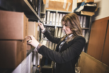 Woman searching for files at basement - JASF000490