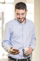 Young man holding coffee looking at cell phone - JASF000493