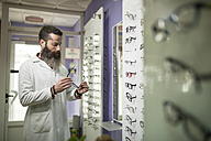 Bearded optometrist in his store looking at glasses - JASF000515