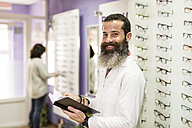 Portrait of smiling bearded optometrist in his store - JASF000521