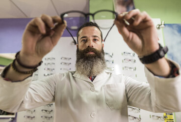 Bearded optometrist in his store looking at glasses - JASF000524