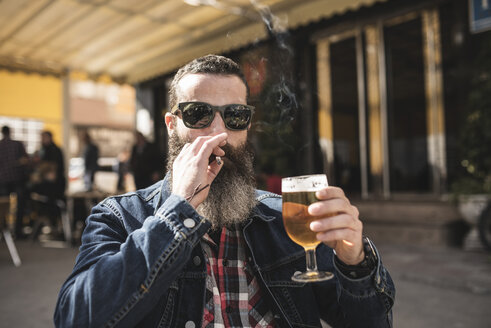 Portrait of bearded man wearing sunglasses smoking  and drinking beer at outdoor gastronomy - JASF000530