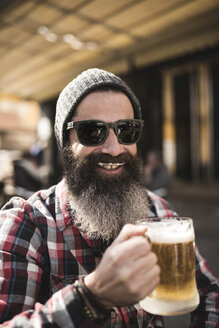 Portrait of smiling hipster with beer foam moustache at outdoor gastronomy - JASF000533
