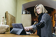 Woman using digital tablet while cooking in her kitchen - JRFF000427