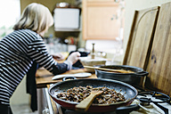 Woman using digital tablet while cooking - JRFF000430
