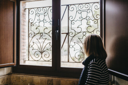 Woman looking through the window of her farmhouse - JRFF000433