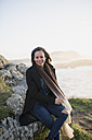 Spain, Ferrol, portrait of smiling  woman sitting on a rock at the coast - RAEF000873