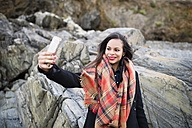 Spain, Ferrol, portrait of smiling  woman taking a selfie with her smartphone in front of rocks - RAEF000879
