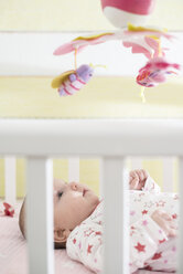 Baby girl lying in a baby cot looking at mobile - DEGF000638