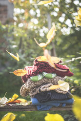 Stack of warm clothing and falling autumn leaves - DEGF000644
