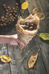 Woman's hand holding paper bag of roasted sweet chestnuts - DEGF000653