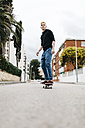 Spain, Torredembarra, smiling young man on his skateboard - JRFF000442