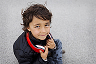 Portrait of little boy with headphones looking up to camera - VABF000159