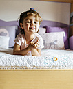 Portrait of little girl lying on her bed - MGOF001436