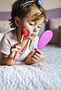 Portrait of little girl lying on bed with  hand mirror and beauty brush - MGOF001439